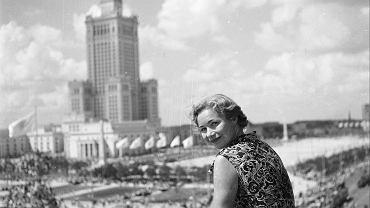 Uczestniczka V Światowego Festiwalu Młodzieży i Studentów pozuje na tle Pałacu Kultury i Nauki, sierpień 1955 roku.