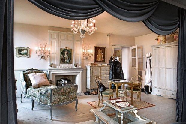 Sypialnia w klimacie buduarowo-teatralnym. Trochę jak scena, którą kurtyna dzieli na dwie części: właściwą z łóżkiem (widocznym na następnej stronie) i wypoczynkową z niezastąpionym szezlongiem. Pod sufitem klasyczny żyrandol murano.