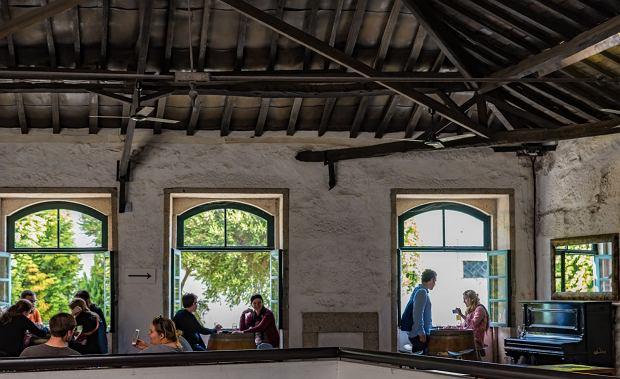 Goście degustujący wino w pomieszczeniu winnicy Quevedo w portugalskim Vila Nova de Gaia
