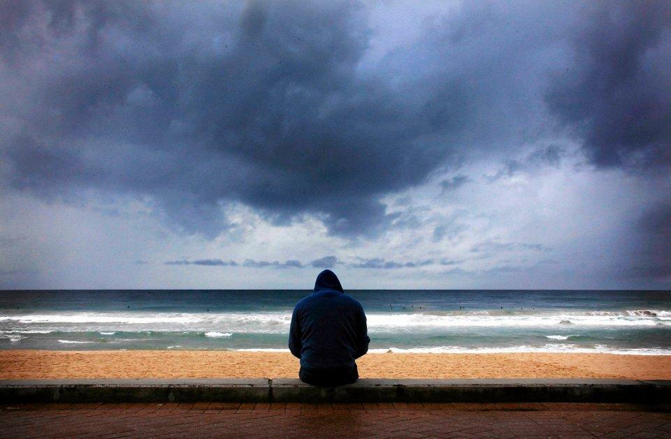 Surfer przygląda się falom i gęstniejącym chmurom burzowym w Sydney. Synoptycy przewidują, że w nadchodzących miesiącach może rozwinąć się wyjątkowo intensywne zjawisko El Nino