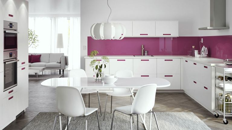Biały owalny stół  ustawiono na dywaniku, wydzielając w ten sposób jadalnię /IKEA