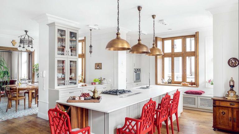 W przejściu między kuchnią a jadalnią pozostawiono komin, resztę otwarto, wyburzając dzielącą ścianę. Umieszczony tam blat ułatwia serwowanie posiłków. Okiennice pozwalają przysłonić okna, a przy tym nadają całości przytulny charakter.