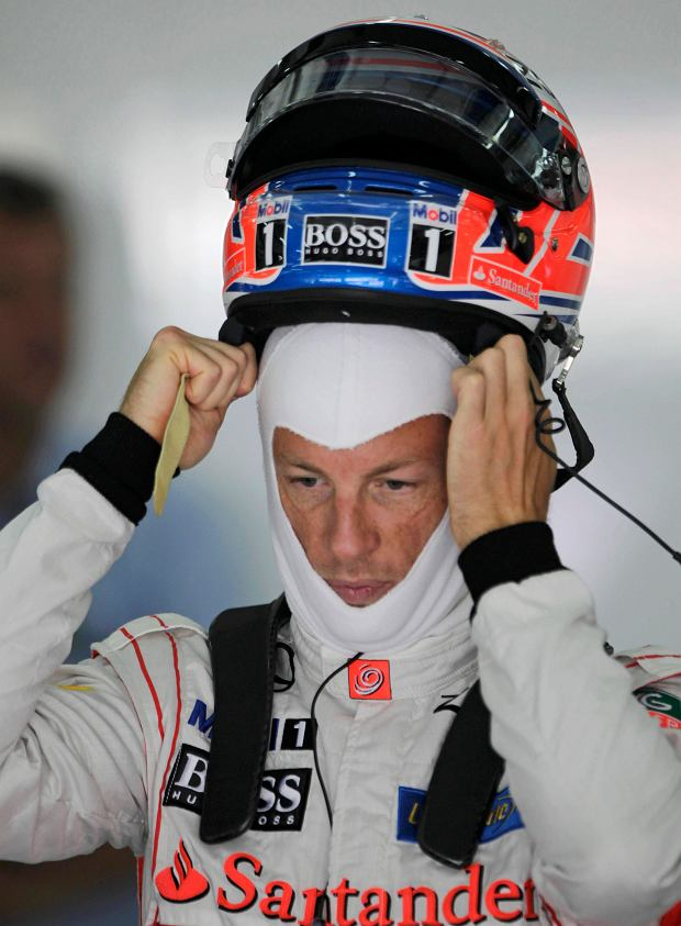 McLaren Formula One driver Jenson Button of Britain puts on his helmet on during the first practice session of the Bahrain F1 Grand Prix at the Sakhir circuit, south of Manama April 19, 2013.  REUTERS/Caren Firouz (BAHRAIN  - Tags: SPORT MOTORSPORT F1)