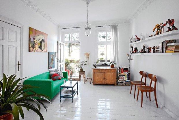 W salonie zachowa�y si� oryginalne sztukaterie. Zielon� kanap� (IKEA) zestawiono z niebieskim stolikiem na k�kach. Kolekcja starych krzese� wizualnie podkre�la galeri� przer�nych zabawek Ma�gorzaty. Lampa stylizowana IKEA, obraz olejny Karoliny.