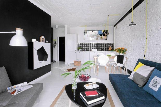 POKÓJ DZIENNY jest utrzymany w bieli i czerni. To zawsze modne, ponadczasowe zestawienie można w każdej chwili ożywić dodatkami w wybranym kolorze. Uwagę zwraca kominek na biopaliwo, którego forma kojarzy się z piłką futbolową. Panorama kamienic nad blatem w kuchni wygląda jak fototapeta, tymczasem to płytki z kolekcji Barcelona projektu Macieja Zienia (dla firmy Tubądzin).