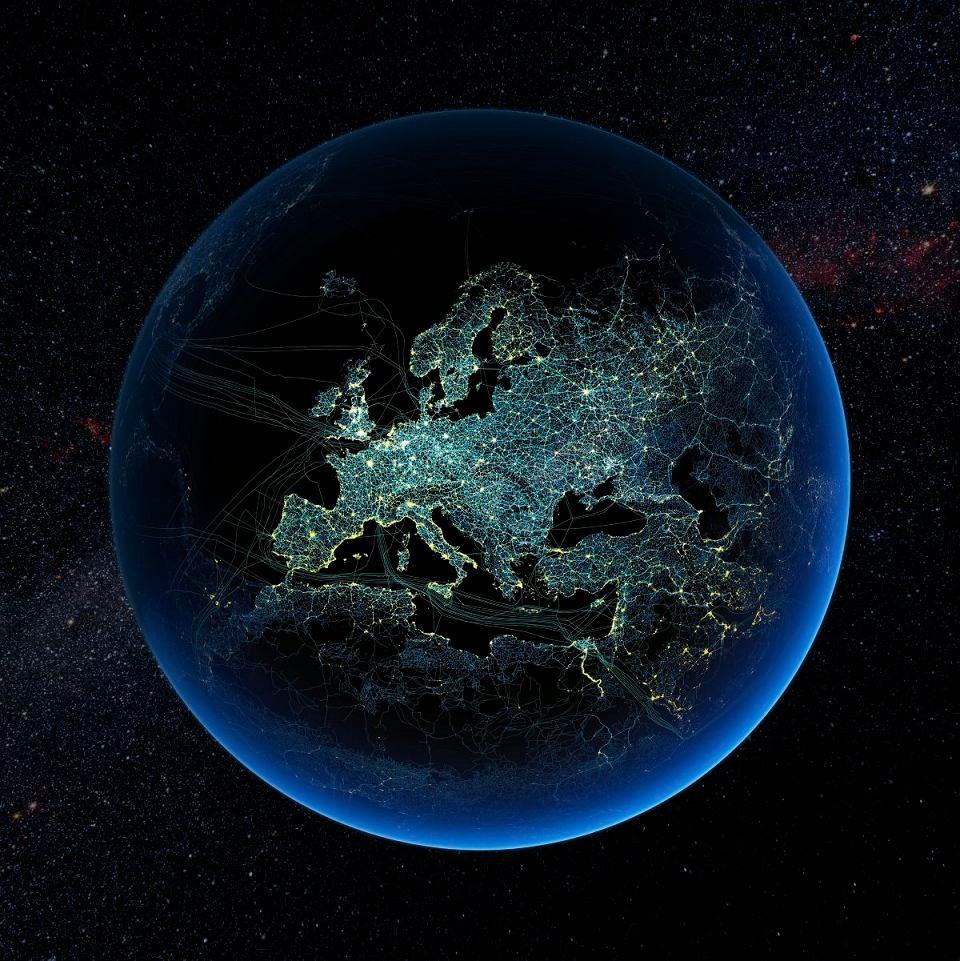Czy żyjemy w antropocenie, geologicznej epoce człowieka? Na ilustracji rozświetlona nocą Ziemia z zaznaczonymi korytarzami transportowymi i podwodnymi liniami przesyłowymi