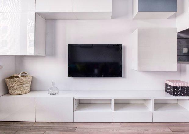 Meble w salonie mają takie same fronty, co szafki kuchenne, co zapewnia we wnętrzu ciągłość stylistyczną.