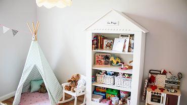 W pokoju dziewczynki został ustawiony mały namiot, w którym uwielbia się bawić swoimi misiami i lalkami. Obok stoi regał w kształcie domu.