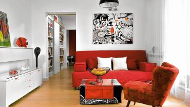 Z białymi ścianami kontrastują meble w mocnych kolorach - sofa (IKEA) i fotel z lat pięćdziesiątych w nowym obiciu (zdobycz z internetu). Abstrakcyjny obraz to po prostu kawałek czarno-białej tkaniny z IKEA, który gospodarze rozpięli na blejtramie i pokolorowali. Stolik kawowy jest dziełem projektantki; zrobiła go z płyty meblowej i 'ubrała' w pokrowiec i bieżnik z kieszeniami. Szufladom w białej komodzie dodano czerwone uchwyty z taśmy pasmanteryjnej - teraz łatwiej je otworzyć.