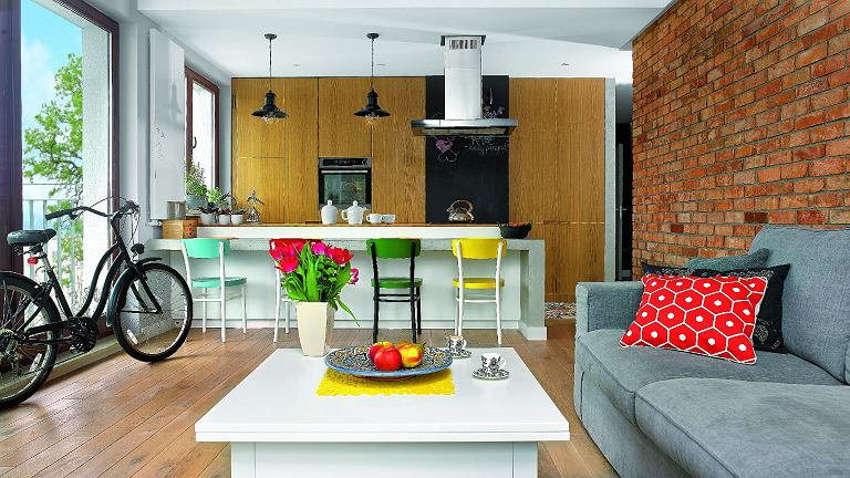 Wnętrze jest przytulne mimo użycia surowych materiałów - cegły ibetonu. Dużo ciepła wprowadziło drewno iakcenty żywych kolorów: przemalowane krzesła przy wyspie (modele Idolf zIKEA) oraz poduszki zModalto i IKEA (na kanapie kupionej wModalto).