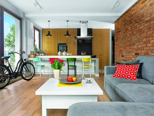WNETRZE JEST PRZYTULNE mimo użycia surowych materiałów - cegły ibetonu. Dużo ciepła wprowadziło drewno iakcenty żywych kolorów: przemalowane krzesła przy wyspie (modele Idolf zIKEA) oraz poduszki zModalto i IKEA (na kanapie kupionej wModalto).