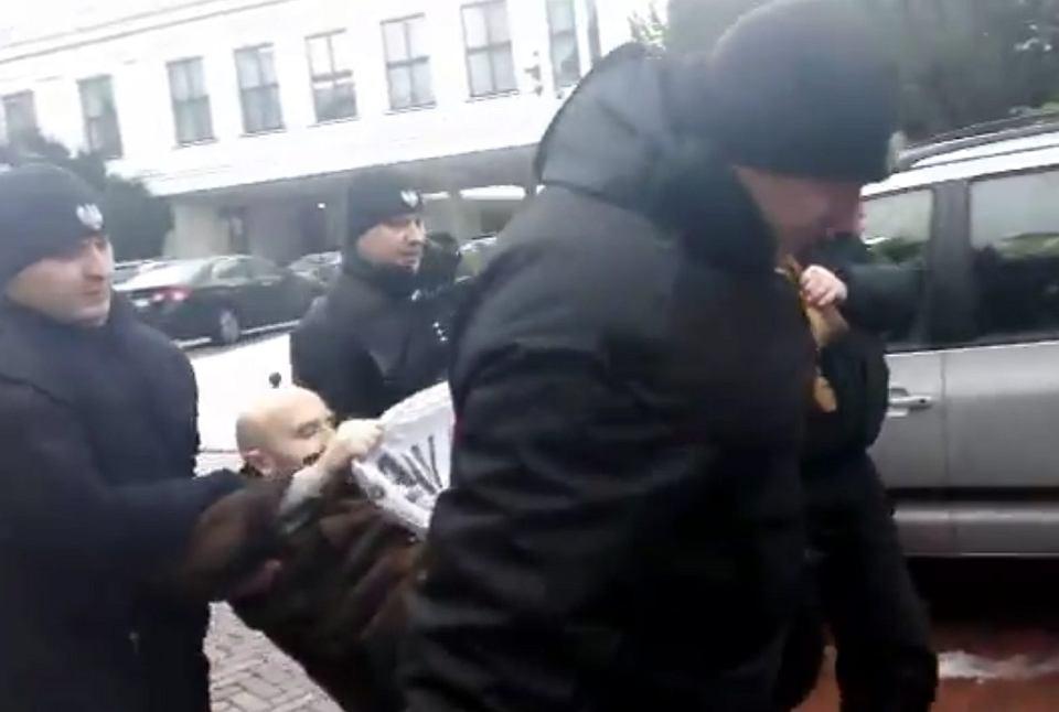 Straż marszałkowska wynosi demonstranta za szlaban parlamentu. Warszawa, 25 stycznia 2017