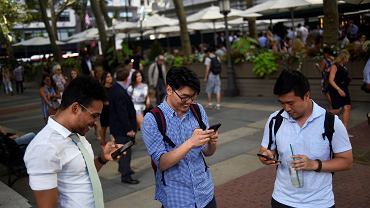 Ludzie w parku w Nowym Jorku, skupieni na grze w Pokemon Go.