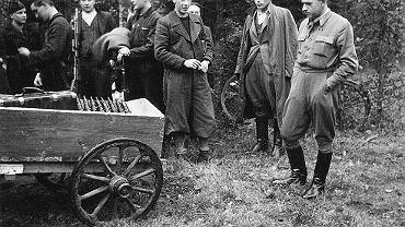"""Ostatnia partia stenów - 21 sztuk dostarczona rano 26.09.1943. Zdjęcie wykonano na Wykusie dwa dni później (28 października 1943 r. rano), tuż przed przewiezieniem stenów na przestrzeliwanie. Za chwile ruszy też niemiecka obława, która przejmie transport, a jako jeden z pierwszych zginie erkaemista """"Kolcik"""" (drugi od lewej). Stoją od lewej: """"Poranek"""" - Józefa Wasilewska, , """"Kolcik"""" - Julian Świtek, """"Bronek"""" - Bronislaw Sianoszek, """"Leszek Bialy"""" - Leszek Zahorski, pchor. """"Andrzej"""" - Andrzej Gawroński, """"Marcysia"""" - Emilia Malessa, żona """"Ponurego"""", """"Jurek-Bazylewicz"""" - Stefan Nawrocki i """"Ponury"""" - Jan Piwnik"""