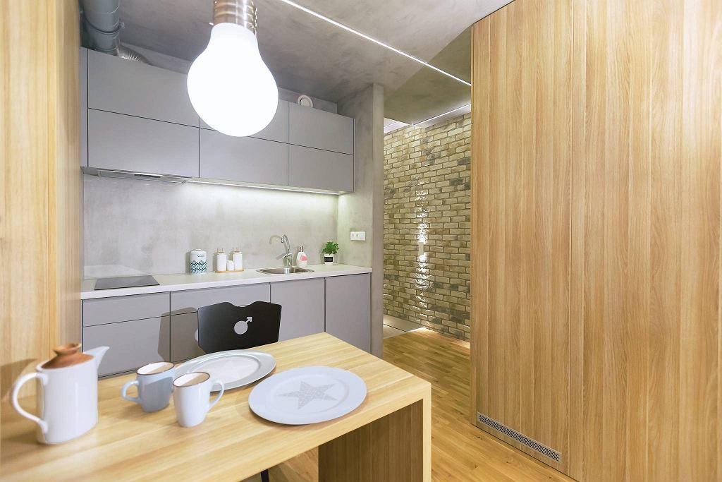 Wnętrze 1. Nad stołem zwiesza się oryginalna lampa w kształcie ogromnej żarówki. Pozostałą część kuchni oświetlają taśmy LED zainstalowane na suficie i pod szafkami wiszącymi.