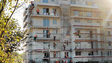 Termomodernizacja - robotnicy podczas prac przy ocieplaniu ściany szczytowej