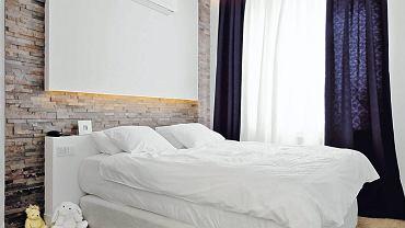 Kamień za łóżkiem - na ścianie wyłożonej naturalnym łupkiem zawieszono prostokąt z płyty gipsowo-kartonowej. W jego dolnym rancie zainstalowano lampki. Zamiast zagłówka jest ścianka, która służy też jako półka.