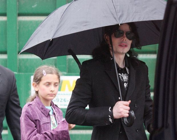 Michael Jackson walks with kids Prince and Paris through a studio parking lot in Los Angeles. The singer had been spotted with his entourage going to a studio on a cold rainy day in LA. Walking through the lot, the kids initially didn't have their usual masks on, it was only after they realized that they could be seen from the street that the kids emerged from a building wearing masquerade type masks. Michael stayed at the studio for over two hours, and there were many production people working around him suggesting that MJ was filming. After some time Michael emerged carrying his own umbrella before getting into his limo and being driven off.