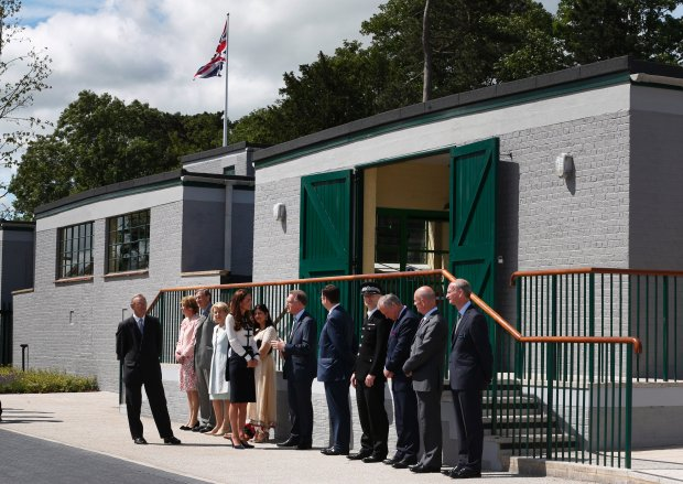 Britain's Kate, Duchess of Cambridge, centre facing right,  meets officials as she arrives for a visit at Bletchley Park, near Milton Keynes, England, Wednesday, June 18, 2014. The Duchess will view the restored location, tour the WWII Codebreaking Huts and will hear about the achievements of the Codebreakers whose work is said to have helped shorten the World War II by two years. (AP Photo/Lefteris Pitarakis)
