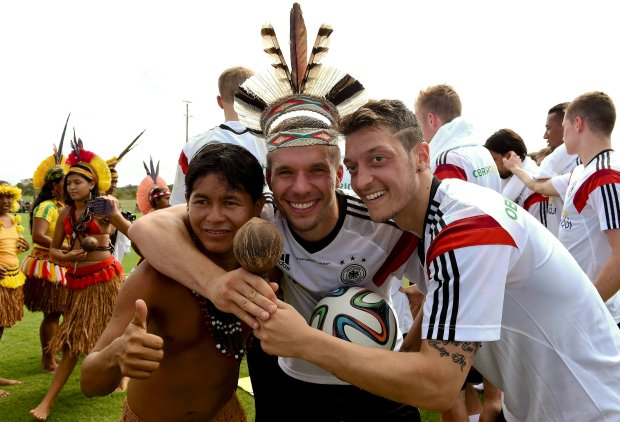 Germany's national soccer players Mesut Oezil (R) and Lukas Podolski (C) pose with a member of a group of native Brazilians after a training session of the German team in the village Santo Andre near Porto Seguro June 9, 2014.  REUTERS/Markus Gilliar/Pool   (BRAZIL  - Tags: SOCCER SPORT WORLD CUP)