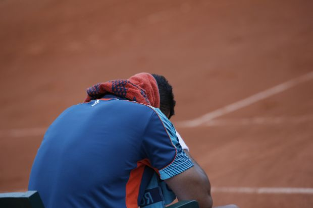 Jo-Wilfried Tsonga of France has towel draped over his head after losing his quarter final match against Novak Djokovic of Serbia at the French Open tennis tournament in Roland Garros stadium in Paris, Tuesday June 5, 2012. Djokovic won in five sets 6-1, 5-7, 5-7, 7-6, 6-1. (AP Photo/Christophe Ena)