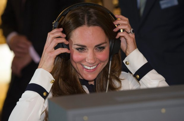 Kate, the Duchess of Cambridge, listens on headphones, during a visit to Bletchley Park, near Milton Keyes, England, Wednesday, June 18, 2014, to mark the completion of the year-long restoration project,  which has restored the site to its World War II appearance. During the visit, Kate met with WWII codebreaker veterans who worked at the Government Code and Cypher School during WWII. (AP Photo/Eddie Mulholland, Pool)