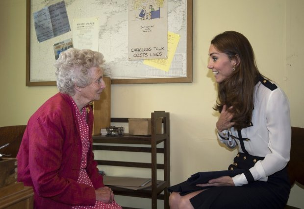 Britain's Catherine, Duchess of Cambridge (R) talks with Bletchley veteran Lady Marion Body (L) who knew her grandmother, Valerie Glassborow, who also worked at the facility during a visit to Bletchley Park in Milton Keynes, north of London, on June 18, 2014 to mark the completion of the year-long restoration project, which has restored the site to its World War II appearance. Bletchley Park was the central site of Britain's Government Code and Cypher School (GC&CS), which during WWII decrypted, translated and analysed encrypted messages sent by the Navy, Army and Air Forces of Germany for vital intelligence. It is thought that the work done by codebreakers at Bletchley Park significantly shortened the duration of the Second World War by as much as years.  AFP PHOTO / POOL / EDDIE MULHOLLAND