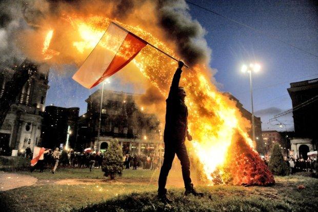 Demonstrant z flagą przed płonącą tęczą na pl. Zbawiciela
