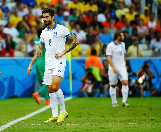 Greece's Panagiotis Kone leaves the field after sustaining an injury during their 2014 World Cup Group C soccer match against Ivory Coast at the Castelao arena in Fortaleza June 24, 2014. REUTERS/Marcelo Del Pozo (BRAZIL  - Tags: SOCCER SPORT WORLD CUP)