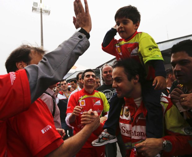 Ferrari Formula One driver Felipe Massa (2nd R) of Brazil carries his son Felipe on his shoulders as he is greeted by fans after the Brazilian F1 Grand Prix at the Interlagos circuit in Sao Paulo November 24, 2013. REUTERS/Nacho Doce (BRAZIL  - Tags: SPORT MOTORSPORT F1)