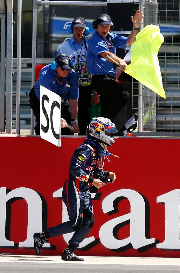 Red Bull Formula One driver Sebastian Vettel of Germany abandons his car after it broke down during the British Grand Prix at the Silverstone Race circuit, central England, June 30, 2013.   REUTERS/Chris Helgren        (BRITAIN - Tags: SPORT MOTORSPORT F1)