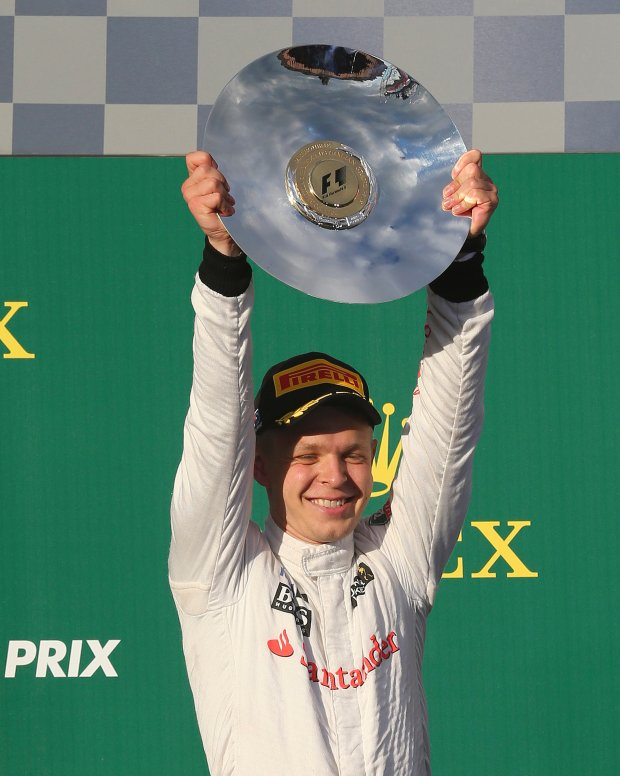 McLaren driver Kevin Magnussen of Denmark holds up his trophy in celebration after finishing third in the Australian Formula One Grand Prix at Albert Park in Melbourne, Australia, Sunday, March 16, 2014. Mercedes driver Nico Rosberg of Germany won the race. (AP Photo/Rob Griffith)