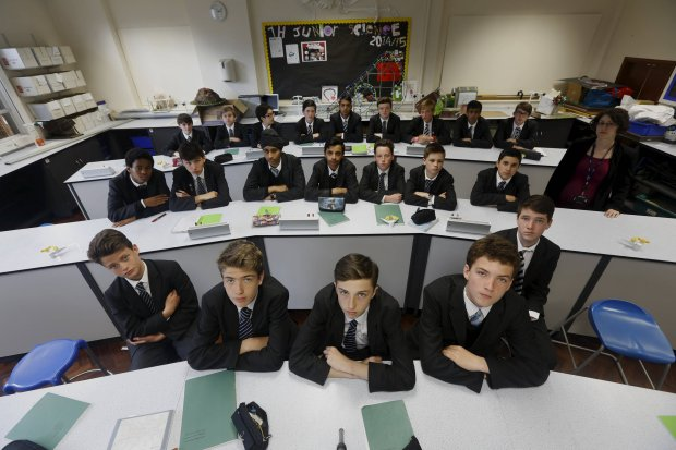 Year 9 Biology boys class pose for a picture with teacher Suzanne Veitch in their classroom at Forest School, London, April 27, 2015. Nearly three years after Taliban gunmen shot Pakistani schoolgirl Malala Yousafzai, the teenage activist last week urged world leaders gathered in New York to help millions more children go to school. World Teachers' Day falls on 5 October, a Unesco initiative highlighting the work of educators struggling to teach children amid intimidation in Pakistan, conflict in Syria or poverty in Vietnam. Even so, there have been some improvements: the number of children not attending primary school has plummeted to an estimated 57 million worldwide in 2015, the U.N. says, down from 100 million 15 years ago. Reuters photographers have documented learning around the world, from well-resourced schools to pupils crammed into corridors in the Philippines, on boats in Brazil or in crowded classrooms in Burundi.     REUTERS/Russell Boyce   TPX IMAGES OF THE DAYPICTURE 11 OF 47 FOR WIDER IMAGE STORY