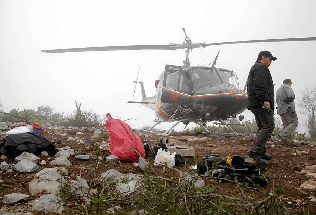 Forensic and criminalistic personnel walk next to a red bag which contains human remains as they inspect the area of the crash site of a plane with Mexican-American singer Jenni Rivera on board, at El Tejocote ranch in the municipality of Iturbide, south of Monterrey, December 10, 2012. Rivera died in a plane crash after the small jet she was travelling in went down in northern Mexico, her father said on Sunday. A spokesman for the state government of Nuevo Leon said investigators had found the remains of Rivera's Learjet, which disappeared from the radar 62 miles (100 km) from the northern city of Monterrey. REUTERS/Daniel Becerril(MEXICO - Tags: DISASTER ENTERTAINMENT) SLOWA KLUCZOWE: :rel:d:bm:GF2E8CB028H01
