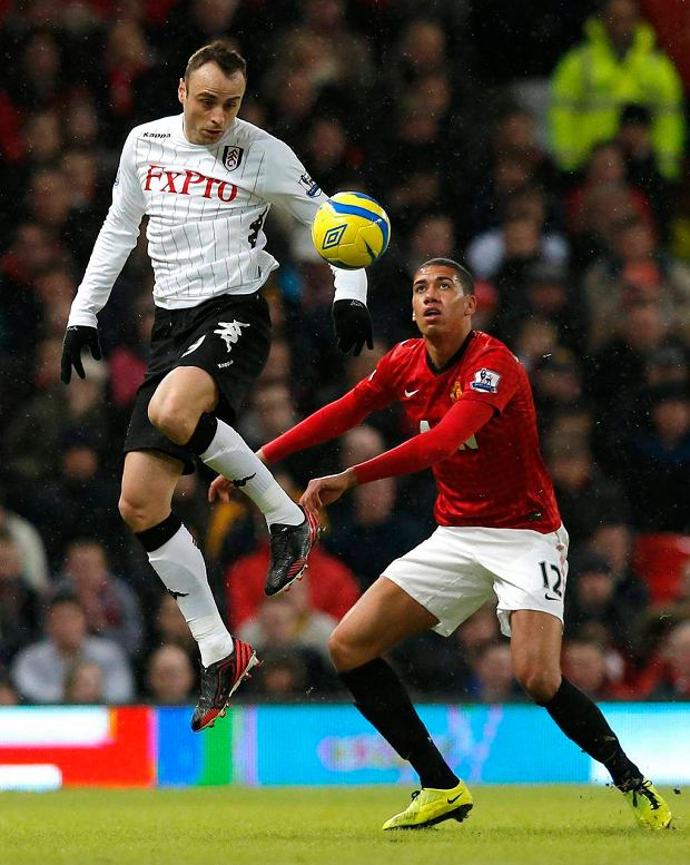 Manchester United's Chris Smalling (R) challenges Fulham's Dimitar Berbatov during their FA Cup fourth round soccer match at Old Trafford in Manchester, northern England, January 26, 2013. REUTERS/Phil Noble (BRITAIN - Tags: SPORT SOCCER) SLOWA KLUCZOWE: :rel:d:bm:GF2E91Q1FBO01