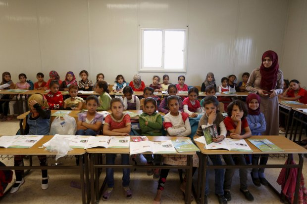 Teacher Hanan Anzi poses for a picture with Syrian refugee students inside their classroom at one of the UNICEF schools at Al Zaatari refugee camp in the Jordanian city of Mafraq, near the border with Syria, September 22, 2015. Nearly three years after Taliban gunmen shot Pakistani schoolgirl Malala Yousafzai, the teenage activist last week urged world leaders gathered in New York to help millions more children go to school. World Teachers' Day falls on 5 October, a Unesco initiative highlighting the work of educators struggling to teach children amid intimidation in Pakistan, conflict in Syria or poverty in Vietnam. Even so, there have been some improvements: the number of children not attending primary school has plummeted to an estimated 57 million worldwide in 2015, the U.N. says, down from 100 million 15 years ago. Reuters photographers have documented learning around the world, from well-resourced schools to pupils crammed into corridors in the Philippines, on boats in Brazil or in crowded classrooms in Burundi. REUTERS/ Muhammad HamedPICTURE 17 OF 47 FOR WIDER IMAGE STORY