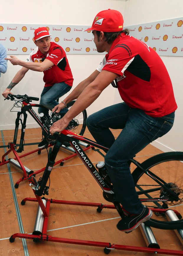 Ferrari driver Kimi Raikkonen of Finland, left, points as he chats with teammate Fernando Alonso of Spain while riding on exercise bikes that generate power for a small slot car set during a publicity event ahead of the Formula One Australian Grand Prix at Albert Park in Melbourne, Australia, Wednesday, March 12, 2014. (AP Photo/Rob Griffith)