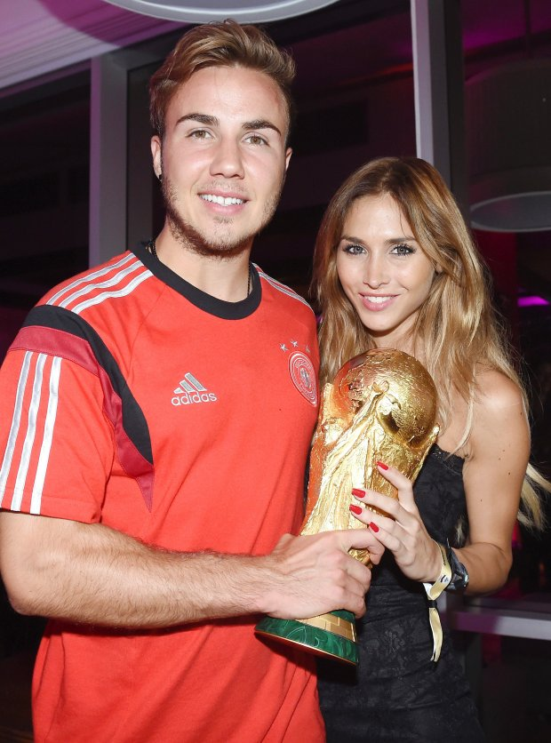 Photo provided by Germany soccer federation DFB shows, from left, Germany's Mario Goetze and his girl friend Ann-Kathrin Broemmel, right, as they hold the trophy during the party of the German soccer federation after Germany beat Argentina 1-0 after extra-time in the soccer World Cup final to win its fourth title in Rio de Janeiro, Brazil, Sunday, July 13, 2014. (AP Photo/DFB, Markus Gilliar, pool)