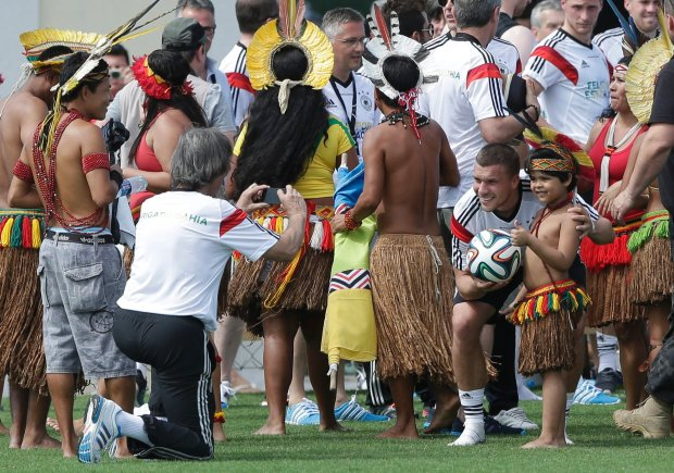 German's national soccer team doctor Hans-Wilhelm Mueller-Wohlfahrt, left, takes pictures of player Lukas Podolski and a young Brazilian indigenous after a training near Porto Seguro, Brazil, Monday, June 9, 2014. Germany will play in group G of the 2014 soccer World Cup. (AP Photo/Matthias Schrader)