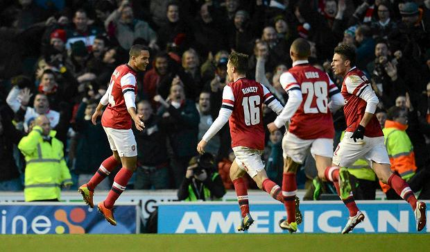 Arsenal's Theo Walcott (L) leaps and celebrates after scoring his team's third goal during their FA Cup fourth round soccer match against Brighton and Hove Albion in Brighton, southern England January 26, 2013. REUTERS/Philip Brown  (BRITAIN - Tags: SPORT SOCCER) SLOWA KLUCZOWE: :rel:d:bm:GF2E91Q1BHQ01