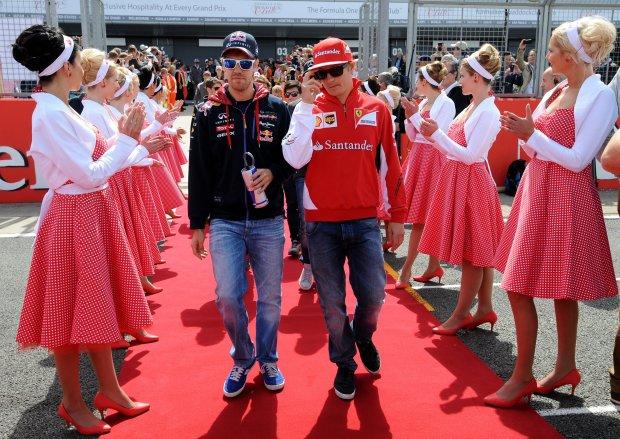 Germany's Sebastian Vettel of Red Bull, left, and Finland's Kimi Raikkonen, right, of Ferrari arrive for the drivers's parade ahead of Formula One British Grand Prix at Silverstone, England, Sunday, July 6, 2014. (AP Photo/Rui Vieira)