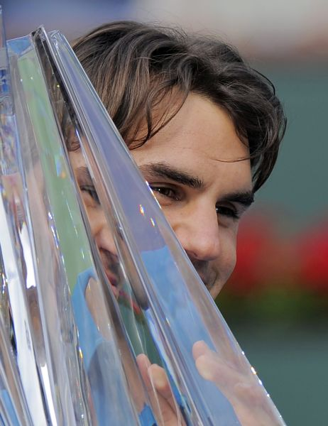 Roger Federer, of Switzerland, holds up his trophy after defeating John Isner, of the United States, in their finals match at the BNP Paribas Open tennis tournament, Sunday, March 18, 2012, in Indian Wells, Calif. Federer won 7-6 (7), 6-3. (AP Photo/Mark J. Terrill)