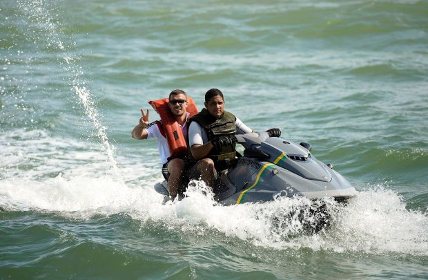 Germany's national soccer player Lukas Podolski (L) makes the victory sign from a jet ski after a tour on the sailing ship 'Pangaea' near the village of Santo Andre, near Porto Seguro June 10, 2014.  REUTERS/Markus GilliarPool (BRAZIL  - Tags: SOCCER SPORT WORLD CUP)