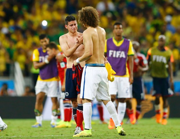 Brazil's David Luiz (R) consoles Colombia's James Rodriguez as they exchange jerseys after their 2014 World Cup quarter-finals at the Castelao arena in Fortaleza July 4, 2014. REUTERS/Marcelo Del Pozo (BRAZIL  - Tags: TPX IMAGES OF THE DAY SOCCER SPORT WORLD CUP)