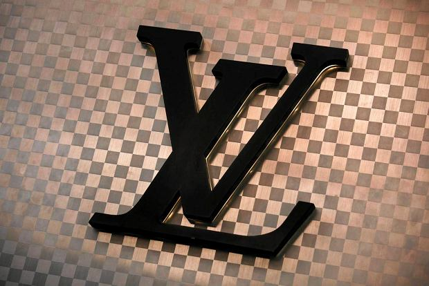 A Louis Vuitton logo is seen outside the store at Hong Kong's Tsim Sha Tsui shopping district March 10, 2013. The luxury good brand angered netizens early this week by demanding HK25,000 ($3,205) compensation from the owner of a local hair salon of trademark infringement after he was found to have chairs covered in what appeared to be the French label's trademarked check pattern, local media reported on Tuesday.   (CHINA - Tags: CRIME LAW BUSINESS SOCIETY CIVIL UNREST LOGO) SLOWA KLUCZOWE: :rel:d:bm:GF2E93A11YT01