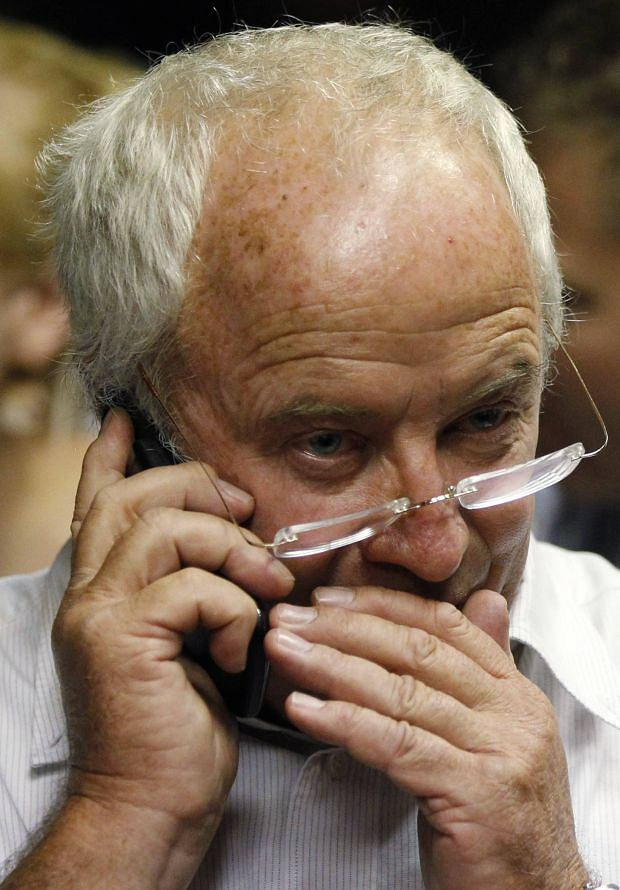Henke Pistorius, father of South African 'Blade Runner' Oscar Pistorius speaks on a mobile phone ahead of his son's court appearance in Pretoria February 15, 2013. Pistorius, a double amputee who became one of the biggest names in world athletics, broke down in tears on Friday after he was charged in court with shooting dead his girlfriend, 30-year-old model Reeva Steenkamp, in his Pretoria house. Pistorius disputes the murder charge laid against him on Friday