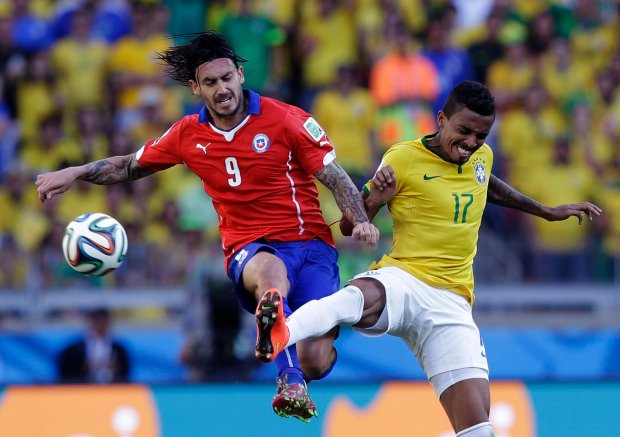 Chile's Mauricio Pinilla, left, and Brazil's Luiz Gustavo battle for the ball during the World Cup round of 16 soccer match between Brazil and Chile at the Mineirao Stadium in Belo Horizonte, Brazil, Saturday, June 28, 2014. (AP Photo/Andre Penner)