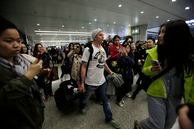 CORRECTS DATE - Lotus driver Kimi Raikkonen, center, of Finland is surrounded by his fans upon his arrival at Pudong International Airport ahead of Chinese Formula One Grand Prix in Shanghai, China Thursday, April 11, 2013. (AP Photo/Eugene Hoshiko)