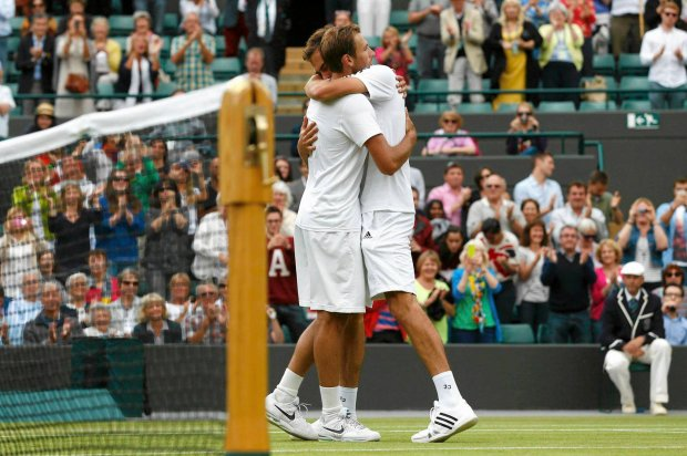 Jerzy Janowicz of Poland (R) embraces Lukasz Kubot of Poland after defeating him in their men's quarter-final tennis match at the Wimbledon Tennis Championships, in London July 3, 2013.             REUTERS/Eddie Keogh (BRITAIN  - Tags: SPORT TENNIS)   SLOWA KLUCZOWE: :rel:d:bm:LR2E9731BPOEQ