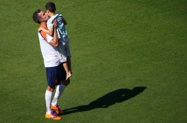 Netherlands' Robin Van Persie kisses his child Shaqueel after a training session in Rio de Janeiro June 24, 2014.  REUTERS/Ricardo Moraes (BRAZIL  - Tags: SPORT SOCCER WORLD CUP)